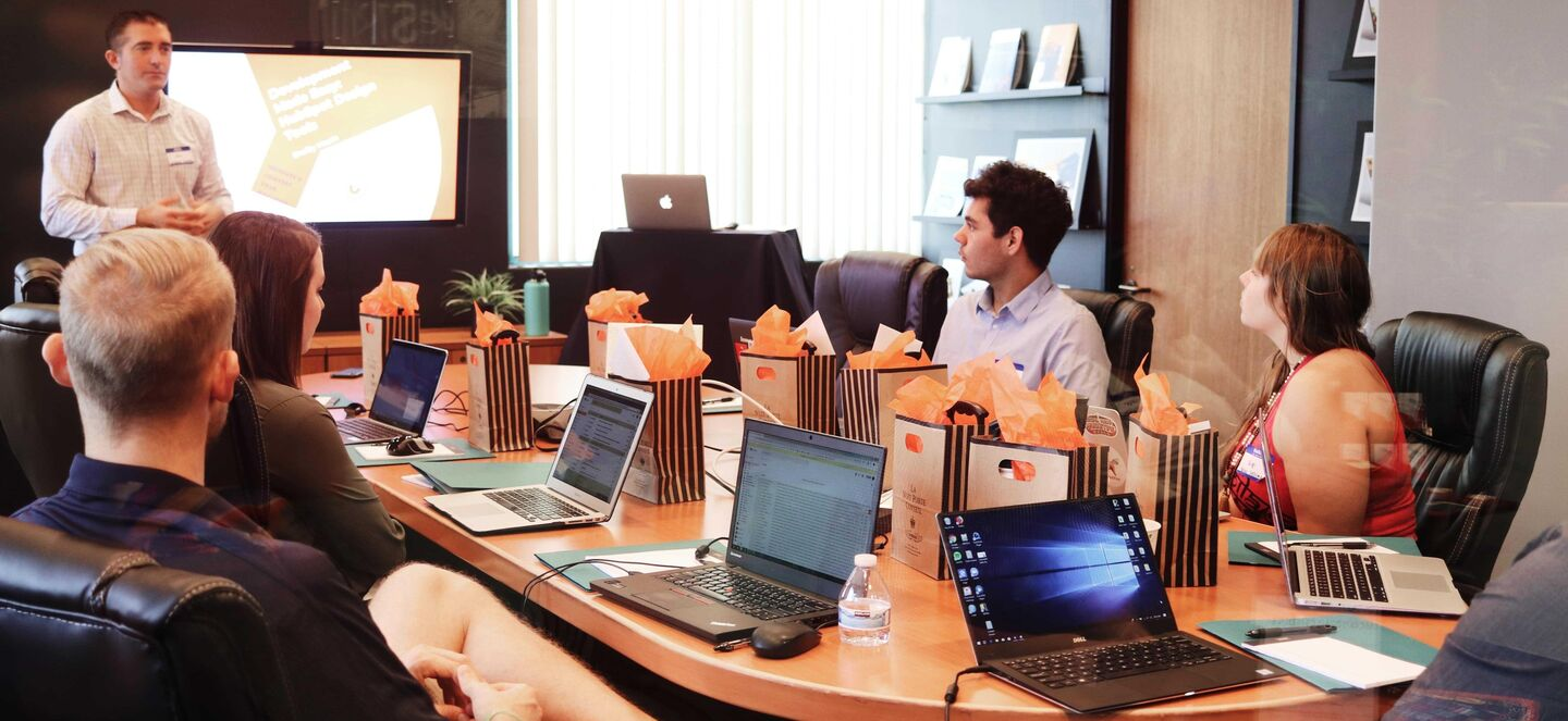 Man giving a presentation to a group of 4 people sitting around a table with laptops in front of them.